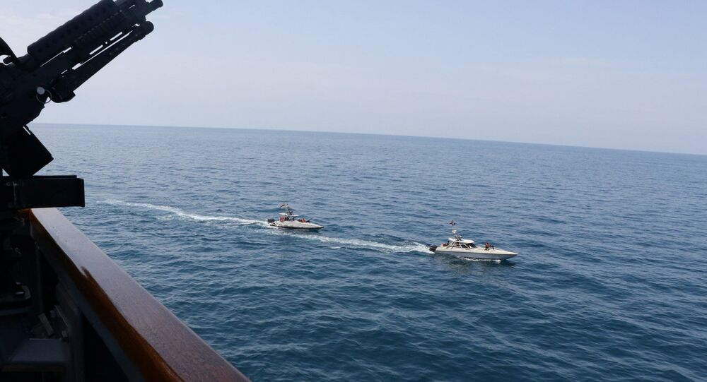 Two Iranian Islamic Revolutionary Guard Corps Navy (IRGCN) vessels, some of several to maneuver in what the U.S. Navy says are unsafe and unprofessional actions against U.S. Military ships by crossing the ships' bows and sterns at close range is seen next to the guided-missile destroyer USS Paul Hamilton in the Gulf April 15, 2020