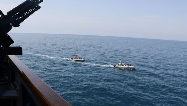 Two Iranian Islamic Revolutionary Guard Corps Navy (IRGCN) vessels, some of several to maneuver in what the U.S. Navy says are unsafe and unprofessional actions against U.S. Military ships by crossing the ships' bows and sterns at close range is seen next to the guided-missile destroyer USS Paul Hamilton in the Gulf April 15, 2020 - Sputnik International