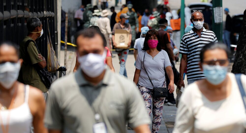 People wearing protective masks walk on a street during a nationwide quarantine as the spread of the coronavirus disease (COVID-19) continues, in Caracas, Venezuela April 20, 2020.