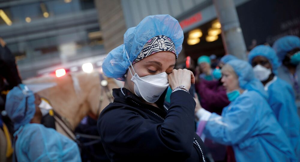 A nurse wipes away tears as she stands outside NYU Langone Medical Center on 1st Avenue in Manhattan as New York Police Department (NYPD) Mounted Police and other units came to cheer and thank healthcare workers at 7pm during the outbreak of the coronavirus disease (COVID-19) in New York City, New York, U.S., April 16, 2020.