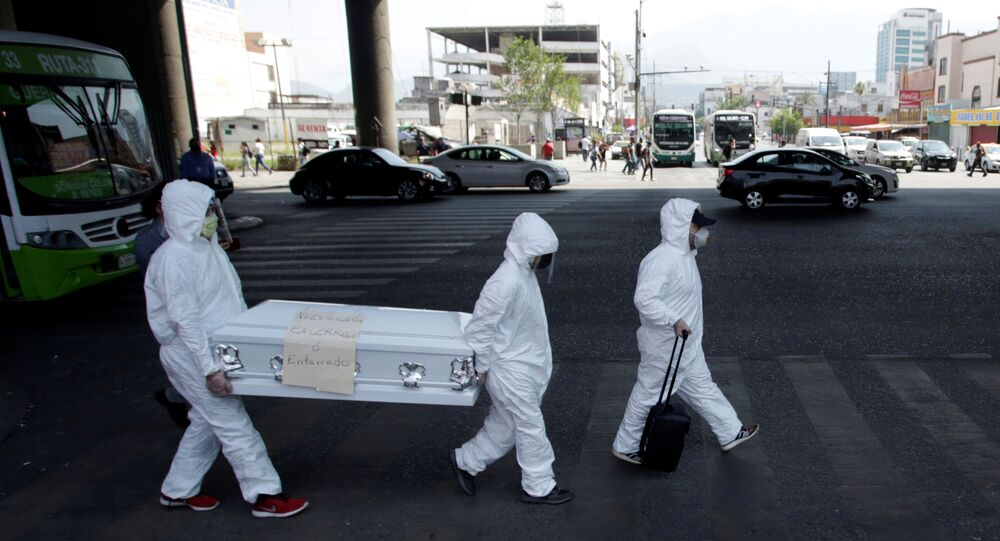 Activists wearing protective suits carry a coffin with a banner attached that says Nuevo Leon locked up or buried as part of an awareness campaign, amid the spread of the coronavirus disease (COVID-19), in Monterrey, Mexico