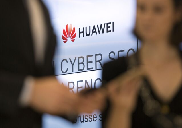 Two people look at their cellphones in front of the Huawei logo during a DigitALL lunch talk in Brussels, Tuesday, May 21, 2019