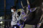 A security guard wearing a mask as a precaution against the new coronavirus stands at the Bombay Stock Exchange (BSE) building in Mumbai, in Mumbai, India, Monday, March 16, 2020