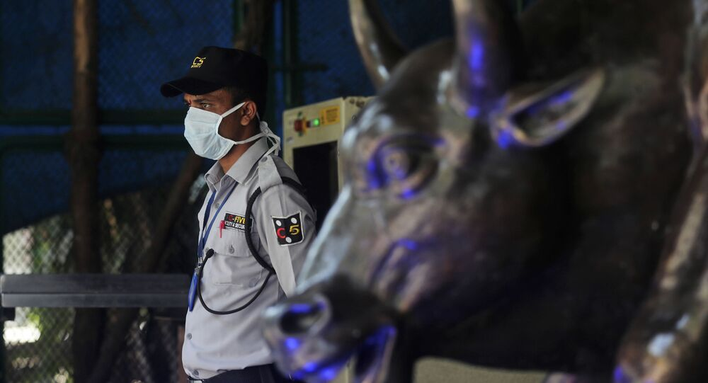 A security guard wearing a mask as a precaution against the new coronavirus stands at the Bombay Stock Exchange (BSE) building in Mumbai, India, Monday, 16 March 2020