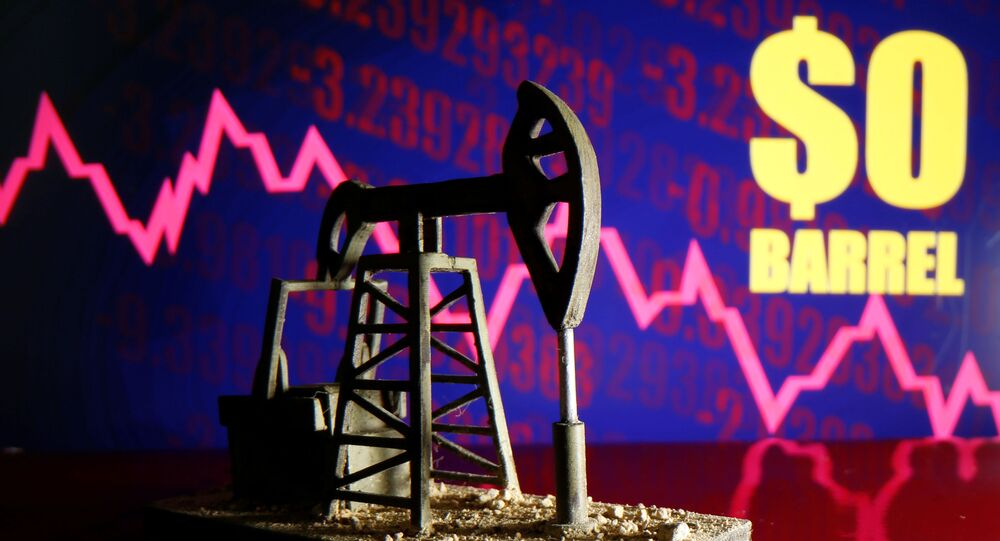 A 3D-printed oil pump jack is seen in front of a displayed stock graph and $0 Barrel words in this illustration picture, April 20, 2020
