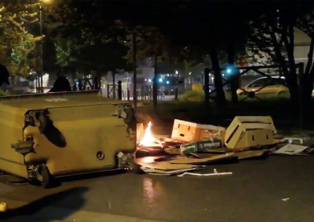 A protester builds a barricade during clashes in Villeneuve-La-Garenne, France April 20, 2020, in this still image obtained from a social media video