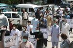 FILE PHOTO: Doctors wearing face masks chant slogans during a protest against the lack of protective gears for medical staff who are treating coronavirus disease (COVID-19) patients in Quetta, Pakistan April 6, 2020