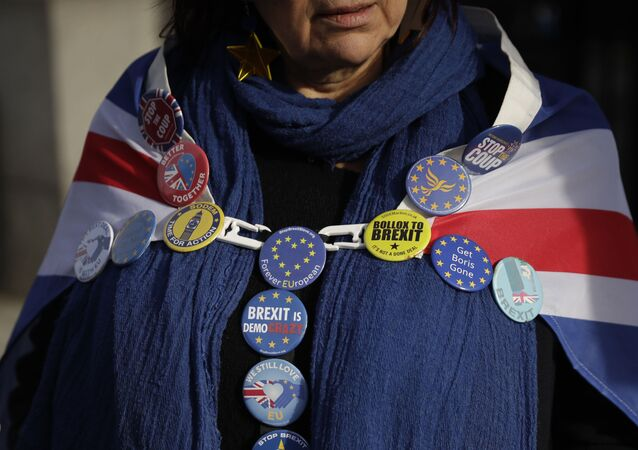 An anti-Brexit remain in the European Union supporter wears badges as she protests outside the Houses of Parliament to coincide with the weekly Prime Minister's Questions at the Houses of Parliament, in London, Wednesday, Feb. 5, 2020