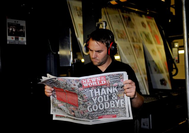 A printer checks the final edition of the News of the World newspaper as it rolls off the press in July 2011