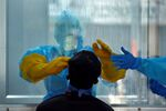 A doctor in a protective chamber takes a swab from a man to test for coronavirus disease (COVID-19) in India