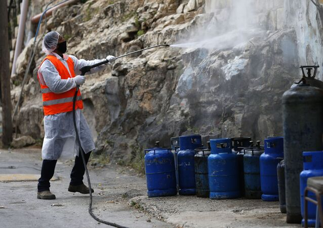Palestinian worker sprays disinfectant as a preventive measure to help contain the coronavirus, in the West Bank city of Nablus, Wednesday, April 8, 2020.