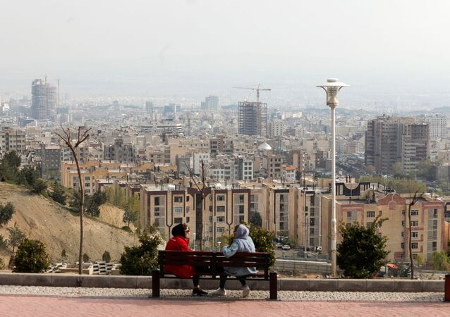 A general view of Tehran is seen as women sit on a bench, in Tehran, Iran April 15, 2020