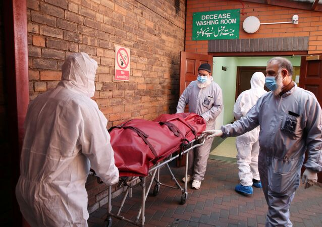 Workers wearing protective equipment transport a body in the grounds of the Central Jamia Mosque Ghamkol Sharif, a temporary morgue set up at a Mosque as the spread of the coronavirus disease (COVID-19) continues, Birmingham, Britain, April 21, 2020.