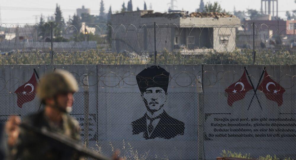 A Turkish soldier walks past graffiti of modern Turkey's founder Mustafa Kemal Ataturk on a wall at the Syrian border.
