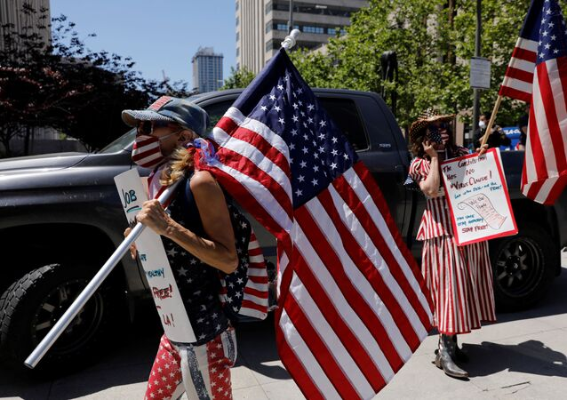 Demonstrators wearing face masks carry placards and U.S. flags as they attend a vehicle caravan protest to call on state and local officials to re-open the economy, during the coronavirus disease (COVID-19) outbreak, near Los Angeles City Hall, Los Angeles, California, U.S., April 22, 2020.