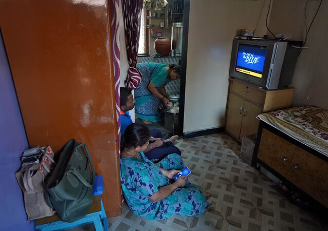Suvarna Dinesh Rasal, 45, a nurse at Breach Candy Hospital Trust watches TV with her son Atharva Dinesh Rasal, 21, who works at a coffee shop, as Aparna Arvind Lanjekar, 68, mother of Suvarna prepares food as they stay indoors inside their single room apartment at a Chawl, home to hundreds of families, during a 21-day nationwide lockdown to slow the spreading of Coronavirus disease (COVID-19), in Mumbai, India March 31, 2020.