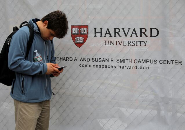 A man looks at his mobile phone beside a sign for Harvard University in Cambridge, Massachusetts, U.S., June 18, 2018.