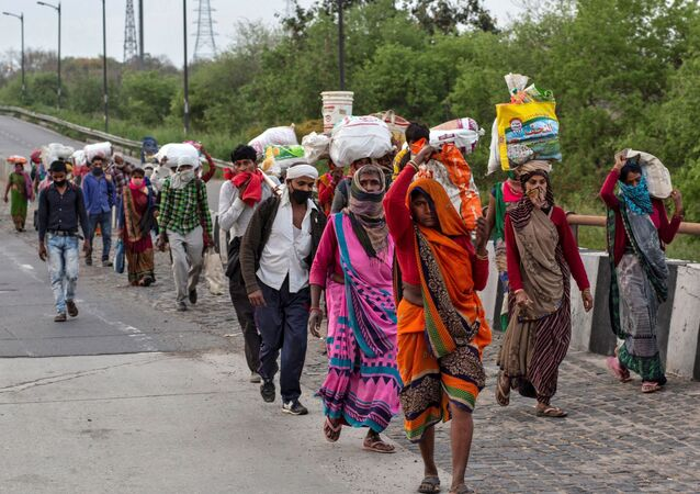 Friends and relatives of Kushwaha family who work as migrant workers walk along a road to return to their villages, during a 21-day nationwide lockdown to limit the spreading of coronavirus, in New Delhi, India, March 26, 2020