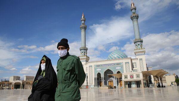 A couple wearing protective face masks, following the outbreak of coronavirus disease (COVID-19), walks on the street in Qom, Iran March 24, 2020 - Sputnik International