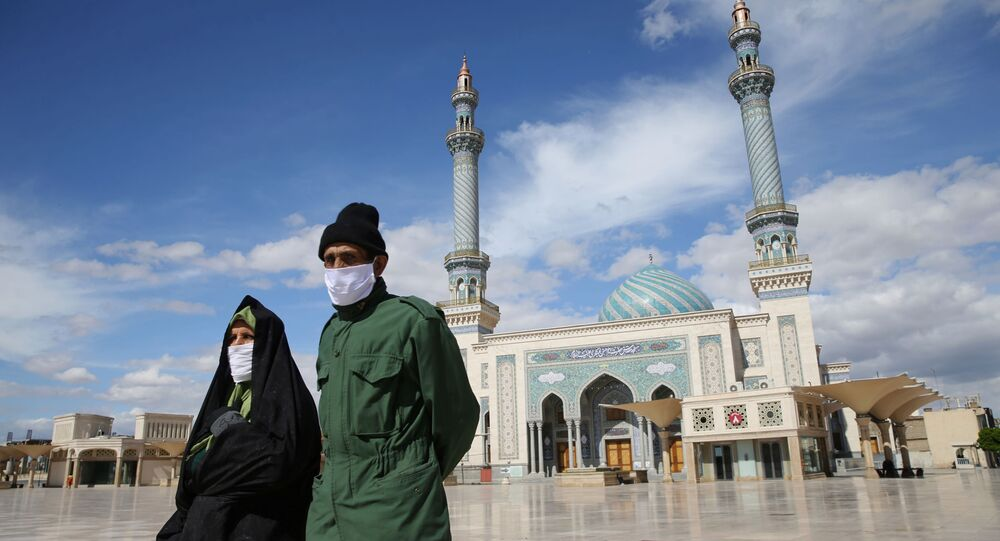 A couple wearing protective face masks, following the outbreak of coronavirus disease (COVID-19), walks on the street in Qom, Iran March 24, 2020