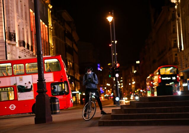 A delivery cyclist checks his phone in Piccadilly Circus during the late evening, as the city at night is deserted like never before while the coronavirus disease (COVID-19) lockdown continues, in London, Britain April 21, 2020