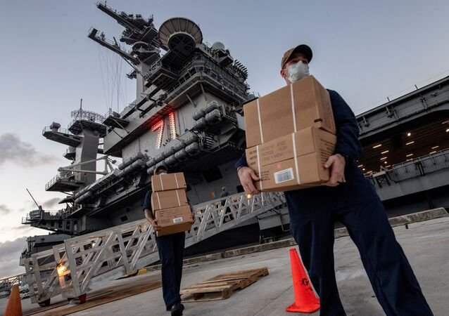 U.S. Navy sailors assigned to the aircraft carrier USS Theodore Roosevelt carry meals in Guam