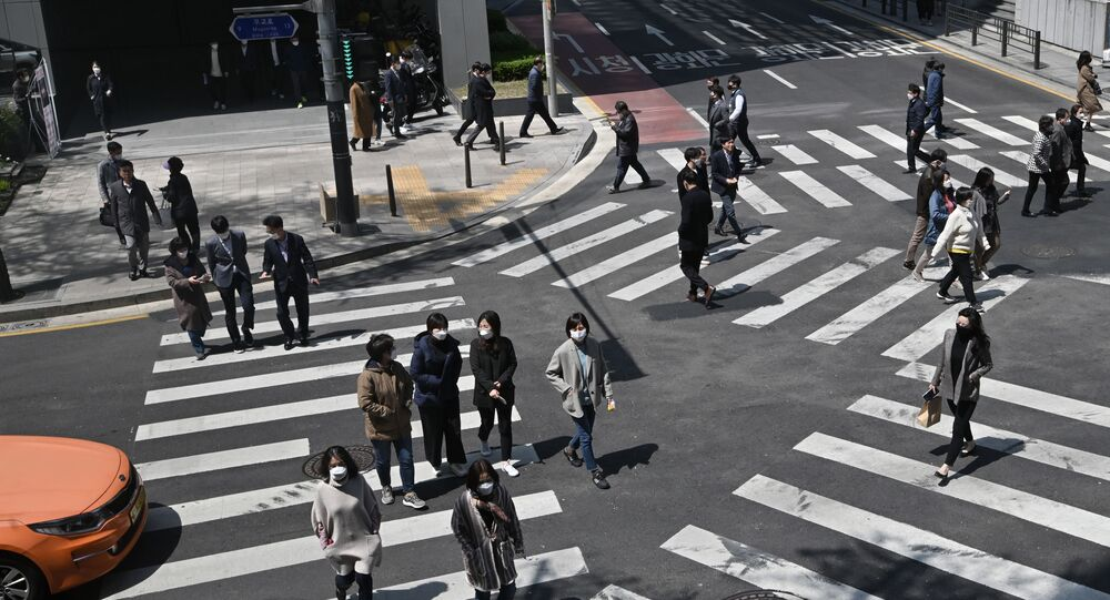 Pedestrians wearing face masks cross the road in Seoul