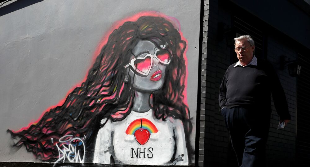 A man passes by a mural in support of the NHS, as the spread of the coronavirus disease (COVID-19) continues, in Redcar, Britain, April 24, 2020.