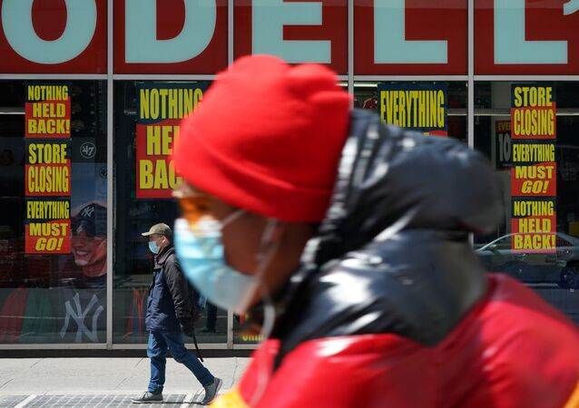 A man wearing a mask rides past a Modell's store that is closed, as retail sales suffer record drop during the outbreak of the coronavirus disease (COVID-19) in New York City, New York, U.S., April 15, 2020.