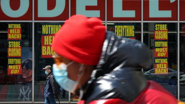 A man wearing a mask rides past a Modell's store that is closed, as retail sales suffer record drop during the outbreak of the coronavirus disease (COVID-19) in New York City, New York, U.S., April 15, 2020.  - Sputnik International
