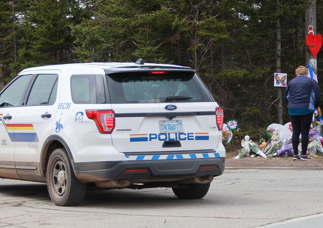 Mourners pay their respects in front of the makeshift memorial, made in the memory for the victims of Sunday's mass shooting as a Royal Canadian Police Vehicle passes nearby in Portapique, Nova Scotia, Canada April 23, 2020