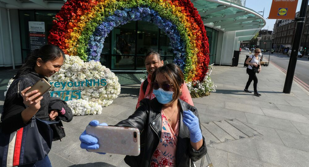 People take a selfie outside University College Hospital next to a rainbow flower display which was organised by the hospital workers to say thank you to the people for their support, during the outbreak of the coronavirus disease (COVID-19) in London, Britain, April 24, 2020.