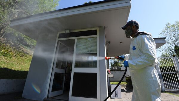 A worker wearing protective clothing is seen spraying disinfectant towards a building in Via Cortina d'Ampezzo in Rome, as the spread of the coronavirus disease (COVID-19) continues, Rome, Italy, April 24, 2020. - Sputnik International