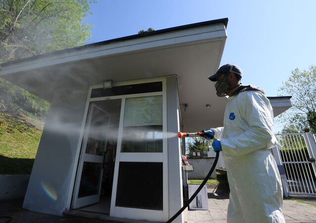 A worker wearing protective clothing is seen spraying disinfectant towards a building in Via Cortina d'Ampezzo in Rome, as the spread of the coronavirus disease (COVID-19) continues, Rome, Italy, April 24, 2020.