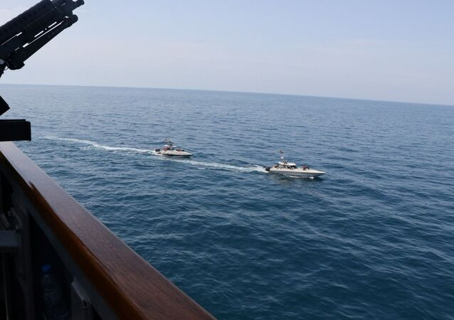 Two Iranian Islamic Revolutionary Guard Corps Navy (IRGCN) vessels, some of several to maneuver in what the U.S. Navy says are unsafe and unprofessional actions against U.S. Military ships by crossing the ships' bows and sterns at close range is seen next to the guided-missile destroyer USS Paul Hamilton in the Gulf April 15, 2020. U.S. Navy/Handout via REUTERS.