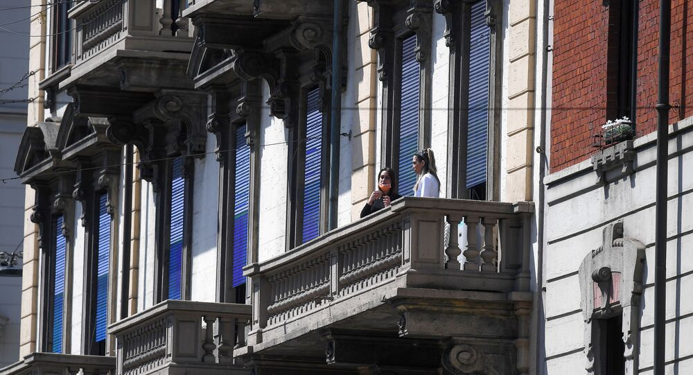 People wearing protective masks are pictured at a balcony during the coronavirus disease (COVID-19) outbreak, in Milan, Italy April 22, 2020.