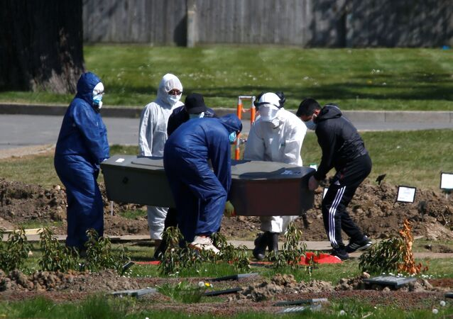 Workers wearing protective suits carry the coffin containing the body of a person at the Muslim cemetery Eternal Gardens in Kemnal Park Cemetery in Chislehurst, as the spread of the coronavirus disease (COVID-19) continues, London, Britain April 23, 2020.