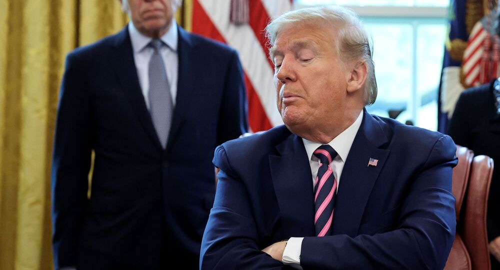 U.S. President Donald Trump looks down at the Paycheck Protection Program and Health Care Enhancement Act, approving additional coronavirus disease (COVID-19) relief for the U.S. economy and hospitals treating people sickened by the pandemic, during a signing ceremony in the Oval Office at the White House in Washington, U.S., April 24, 2020