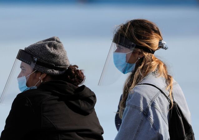 People in face shields sit in Flushing Meadows-Corona Park during the outbreak of the coronavirus disease (COVID-19) in the Queens borough of New York City, U.S., April 25, 2020