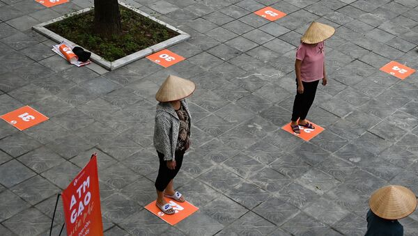 Люди сохраняют дистанцию в целях профилактики коронавируса в очереди за бесплатным рисом в Ханое, Вьетнам - Sputnik International