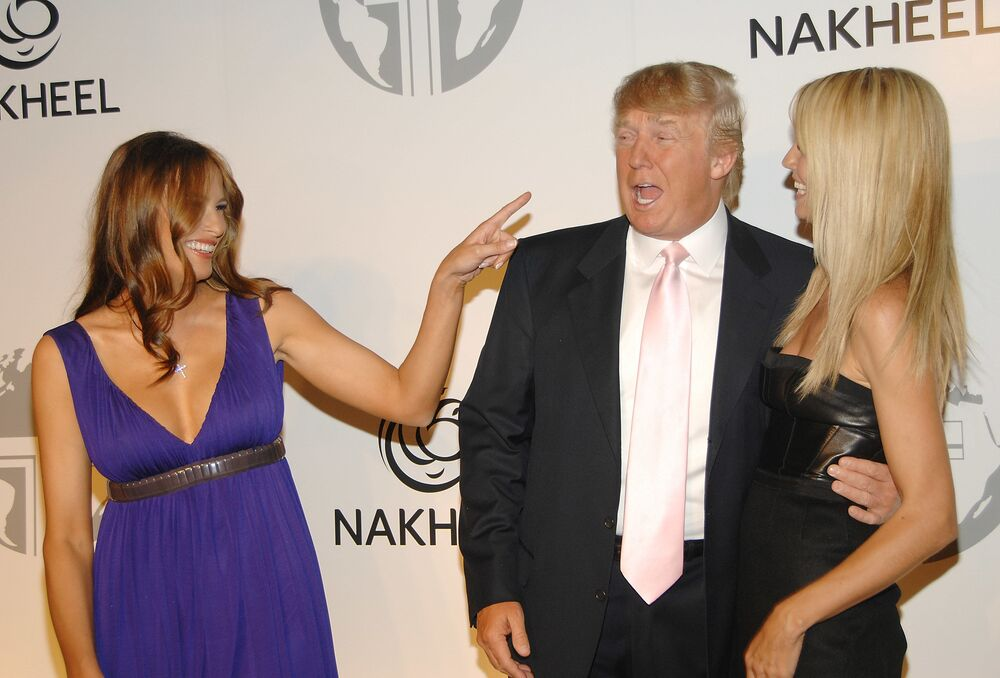 Real estate tycoon Donald Trump, center, gets scolded by his wife Melania, left, while he embraces model Heidi Klum at a party to introduce The Trump International Hotel & Tower Dubai, hosted by the real estate development company Nakheel, on Monday, June 23, 2008 in New York.