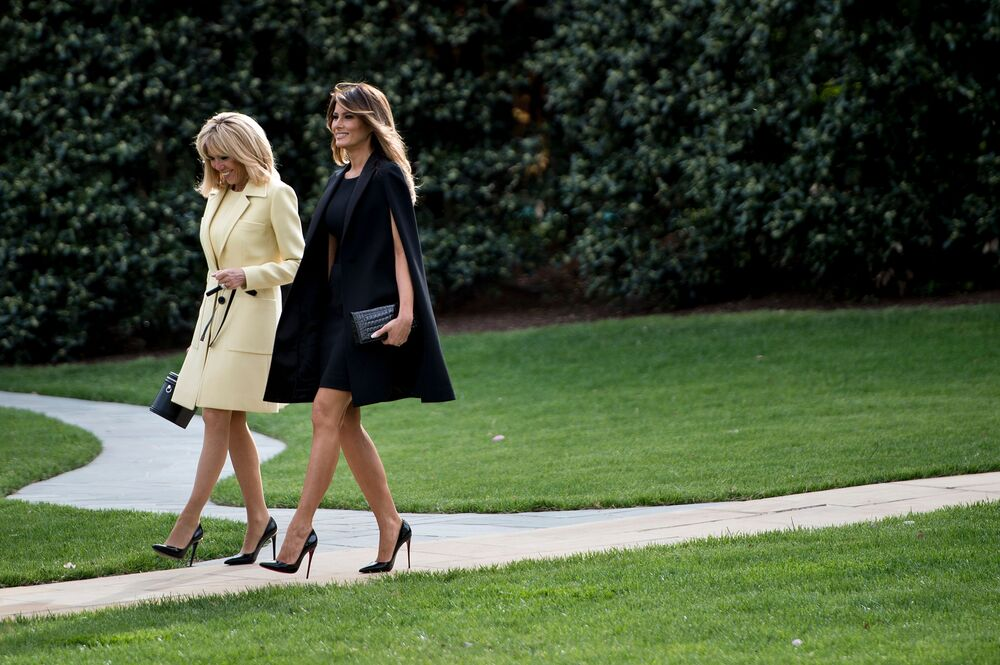 Brigitte Macron and Lady Melania Trump walk after a tree planting ceremony with French President Emmanuel Macron and US President Donald Trump on the South Lawn of the White House in Washington, DC, on April 23, 2018.