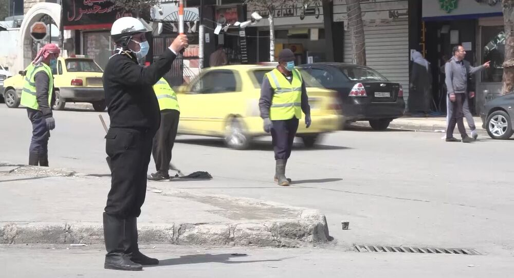 In this handout video grab apolice officer guards in a face mask during the COVID-19 coronavirus disease, in Latakia, Syria.