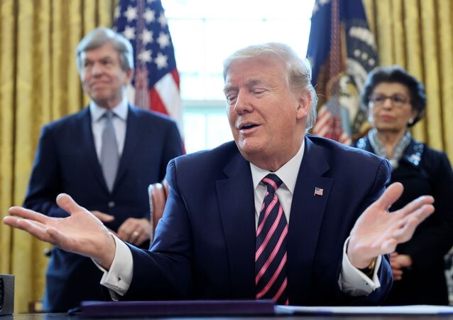 U.S. President Donald Trump speaks to reporters as Senator Roy Blunt (R-MO) and Small Business Administration (SBA) Administrator Jovita Carranza look on during a signing ceremony for the Paycheck Protection Program and Health Care Enhancement Act, approving additional coronavirus disease (COVID-19) relief for the U.S. economy and hospitals treating people sickened by the pandemic, in the Oval Office at the White House in Washington, U.S., April 24, 2020