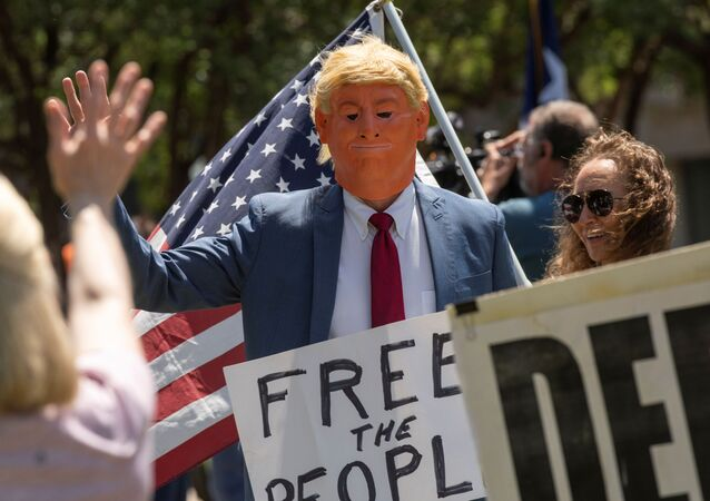 An attendee with a mask dressed to impersonate President Donald Trump walks through the crowd and waves at supporters as a group called Open Texas rally to re-open Texas businesses, places of work and religious services shut down by coronavirus (COVID-19) pandemic restrictions as they gather in a park outside of the City Hall in Frisco, Texas, U.S., April 25, 2020.