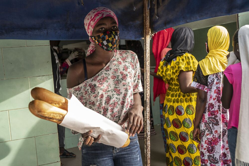 In this photo taken Saturday 25 April 2020 Ndyeye Fatou, the daughter of Bara Tambedou, wears a patterned face mask as she buys bread for her family on the first day of the Muslim holy month of Ramadan, in Dakar, Senegal. This year the family is celebrating Ramadan at home, with prohibitions on public gatherings and a dusk-to-dawn curfew in place to curb the spread of the new coronavirus.