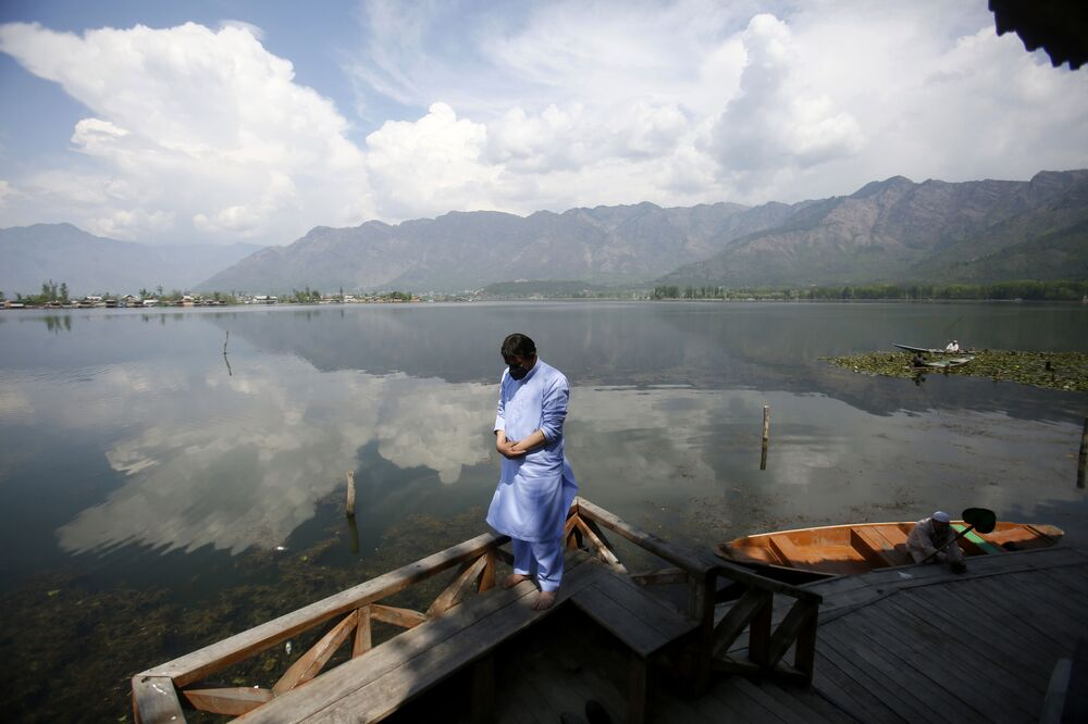 A Kashmiri Muslim man offers prayer on the banks of Dal Lake on the second day of Ramadan during lockdown to prevent the spread of the new coronavirus in Srinagar, Indian controlled Kashmir, Sunday, April 26, 2020.