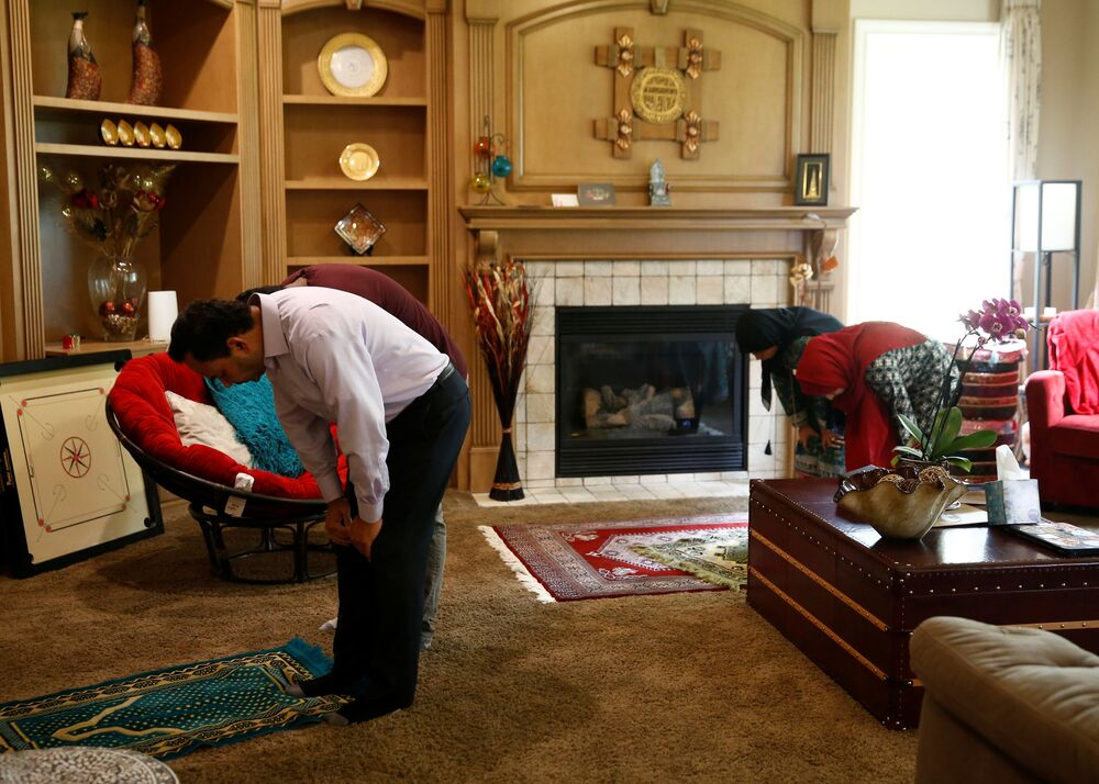 Hyder Ali, the president of the Muslim Association of Puget Sound, prays at home with son Zayaan, 18, daughter Jannah, 13, and wife Yasmin, right, after watching a live-streamed congregational service on the first day of Ramadan during the coronavirus disease (COVID-19) outbreak in Redmond, Washington, US 24 April 2020.