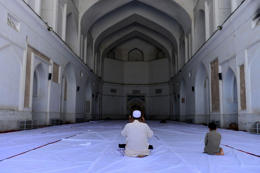 A Muslim man and a child offer prayers during the Islamic holy month of Ramadan at the Jami mosque, in Herat on 26 April 2020.