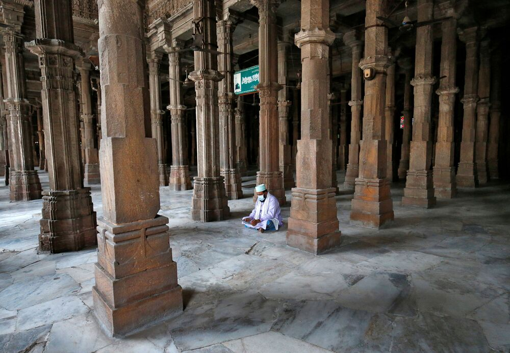A Muslim wearing a protective mask reads the Koran inside Juma Masjid on the first day of the Muslim fasting month of Ramadan, during a nationwide lockdown to slow the spreading of the coronavirus disease (COVID-19), in in Ahmedabad, India 25 April 2020.